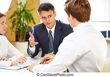 Serious boss giving some information to young office workers