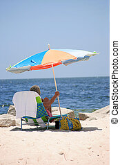 Making Shade - An older woman sitting at the beach under a...