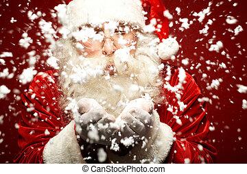 Making snowfall - Photo of Santa Claus in eyeglasses blowing...