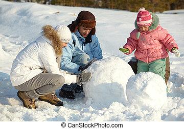 Making snowman - Portrait of family making snowman in park