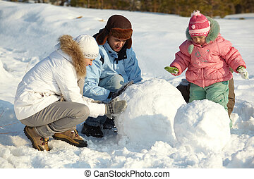 Making snowman - Portrait of family making snowman in park
