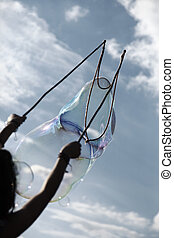 An anonymous woman making giant soap bubbles against cloudy sky background.