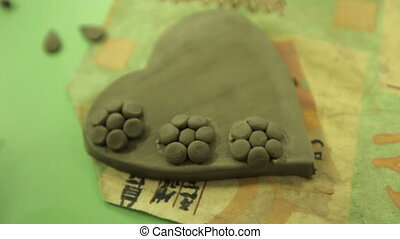 Making souvenirs from clay in an art workshop. A clay heart...