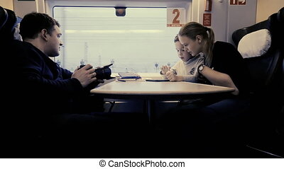 Making stock footage when mom with son playing on pad in train