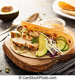Making tacos with grilled chicken and avocado