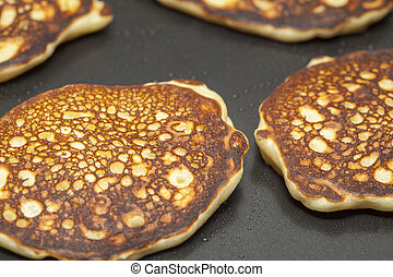 making thick pancakes on dark griddle surface