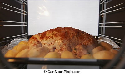 Making whole roasted chicken with potatoes baked in the oven timelapse