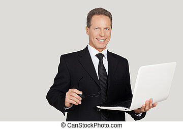 Making your business easy. Cheerful senior man in formalwear holding laptop and smiling while standing against grey background