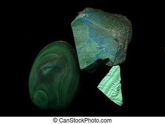 Malachite stone, rough and cut, against a black background