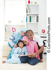 malay family using tablet having a good time surfing internet