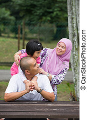 malay muslim family having fun in the park