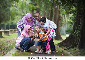 malay muslim family having fun playing in the park