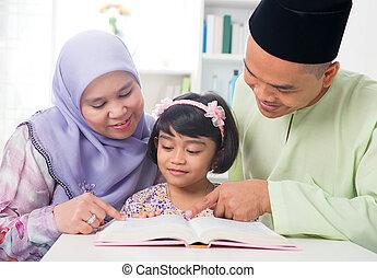 Malay Muslim family reading a book. - Malay Muslim parents...