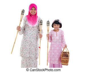 malay sisters with oil lamp during hari raya festival