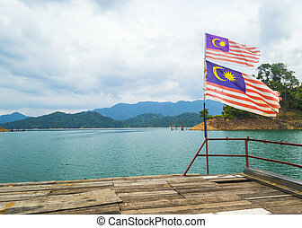 Malaysia flag with tropical island and cloudy skies