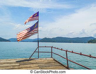 Malaysia flag with tropical island and blue skies