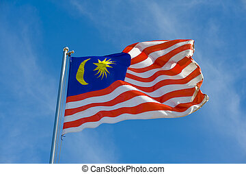 malaysian flag on a pole against blue sky