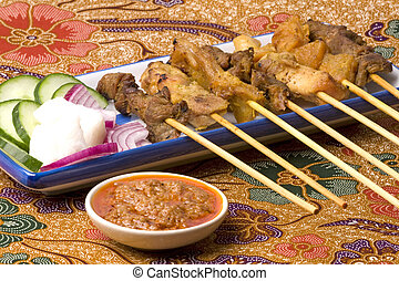 Image of a Malaysian delicacy commonly known as Satay (bamboo stick skewered barbequed meat) placed on a piece of Batik material.