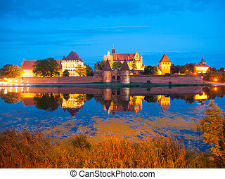 Malbork castle by night with reflection in Nogat river