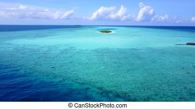 maldives tropical island and blue sea with drone aerial flying view on a beach with white sand and beautiful sky background