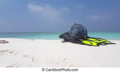 Maldives white sandy beach snorkeling fins mask flippers scuba on sunny tropical paradise island with aqua blue sky sea water ocean 4k