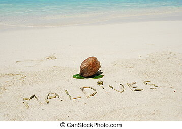 Maldives written in a sandy tropical beach and coconut fruit...