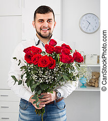 Male 25-30 years old is presenting flowers and gift during romantic date.