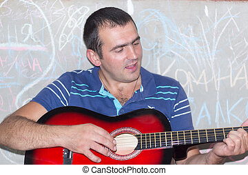 male 30 years old, sits near a painted concrete wall and playing guitar