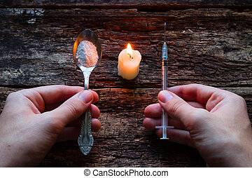 male addict holding syringe and spoon with heroin next to a candle