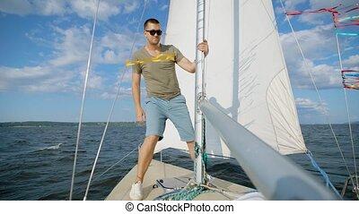 Male adventurer posing on modern sailboat looking away in...