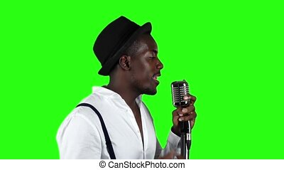 Male african american musician half of the turnover singing in a recording studio. Green screen. Slow motion. Close up