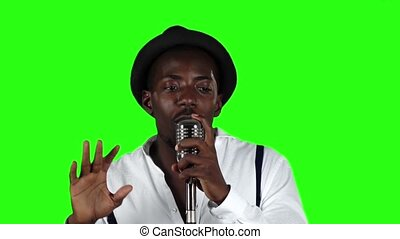 Male african american musician singing in a recording studio...