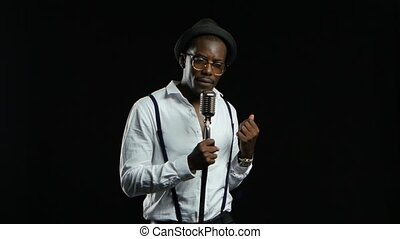 Male african american musician singing in a recording studio. Black background