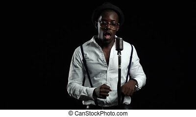 Male african american singer sings into a microphone and dancing. Black background. Slow motion. Close up
