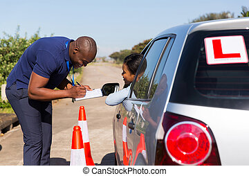 male african driving instructor and student driver in...