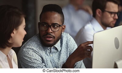 Male African mentor teach female Caucasian intern explain ...