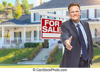 Male Agent Reaching for Hand Shake in Front of House and For Sale Real Estate Sign