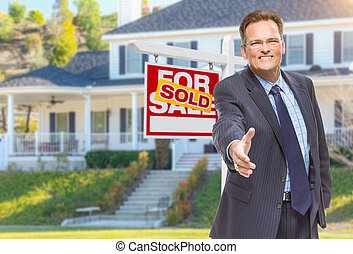 Male Agent Reaching for Hand Shake in Front of House and Sold Real Estate Sign