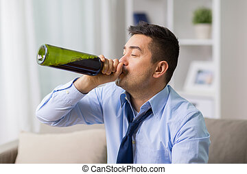 male alcoholic drinking wine from bottle at home