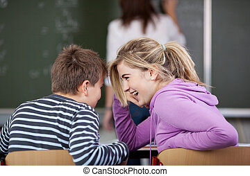 Male and a female student gossiping in classroom