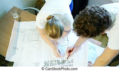 Male and female architects during work with construction...