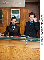 Male and female at hotel reception busy working