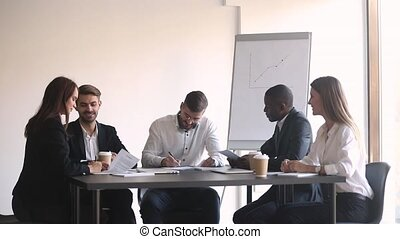 Male and female business partners sign contracts handshake...