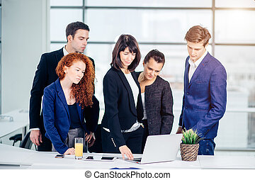 male and female business people around laptop computer in office
