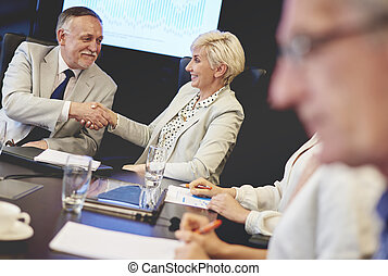 Male and female business worker shaking hands