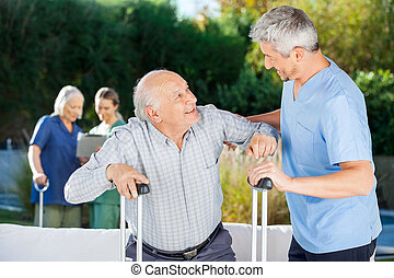 Male And Female Caretakers Helping Elderly People
