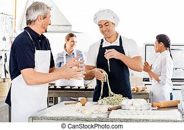 Male And Female Chefs Preparing Pasta In Kitchen