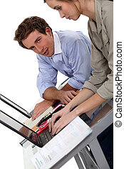 male and female colleagues working on laptop