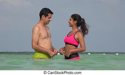 Male And Female Couple Wearing Bathing Suits In Ocean