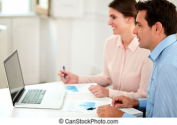 Male and female cowokers looking at laptop